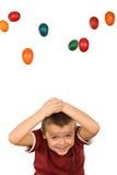Muchacho con los huevos de Pascua que caen Fotos de archivo libres de regalías