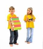 Muchacho con los libros pesados, y una muchacha que tiene un eBook Foto de archivo libre de regalías