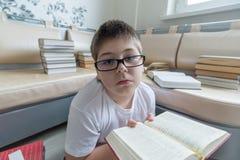 Muchacho con los vidrios que lee un libro en sitio Fotografía de archivo