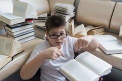 Muchacho con los vidrios que lee un libro en sitio Fotos de archivo
