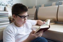 Muchacho con los vidrios que lee un libro en sitio Foto de archivo