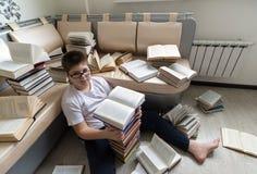 Muchacho con los vidrios que lee un libro en sitio Imagen de archivo