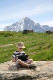 El muchacho con PC de la tableta se sienta en piedra Imagen de archivo libre de regalías