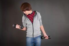 Muchacho con pesas de gimnasia en ropa del ocio Fotos de archivo