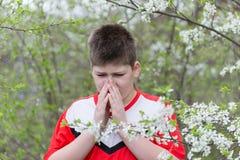 Muchacho con rinitis alérgica en jardín de la primavera Foto de archivo libre de regalías