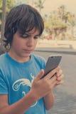 Muchacho con smartphone en la calle Fotografía de archivo