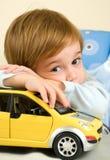 Muchacho con su coche del juguete Foto de archivo
