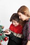 Muchacho con su mamá que adorna el árbol de navidad Foto de archivo libre de regalías