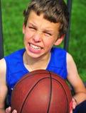 Muchacho con un baloncesto que se sienta en corte Imagenes de archivo