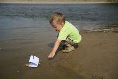 Muchacho con un barco de vela Imagen de archivo