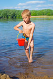 Muchacho con un cubo de agua Imágenes de archivo libres de regalías