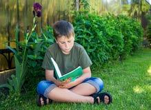Muchacho con un libro en la hierba Foto de archivo