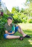 Muchacho con un libro en la hierba Fotos de archivo