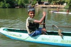 Muchacho con un mono que se bate en su canoa Foto de archivo libre de regalías