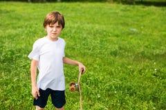 Muchacho con un monopatín, en un fondo de la hierba Imagen de archivo libre de regalías