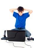 Muchacho con un ordenador portátil y una palanca de mando Foto de archivo
