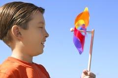 Muchacho con un pinwheel de la rueda de giro Foto de archivo libre de regalías