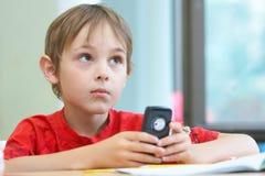 Muchacho con un teléfono Imágenes de archivo libres de regalías