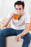 Muchacho con un vidrio de cerveza y teledirigido jovenes Fotos de archivo
