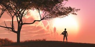 muchacho con una bola y una puesta del sol Foto de archivo libre de regalías