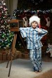 Muchacho con una cámara debajo del árbol de navidad por la chimenea Fotografía de archivo
