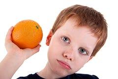 Muchacho con una naranja Imagen de archivo libre de regalías