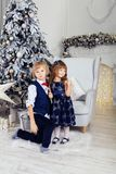 Muchacho con una niña que juega cerca del árbol de navidad El concentrado Foto de archivo libre de regalías