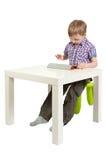 Muchacho con una PC de la tablilla en el escritorio Fotografía de archivo libre de regalías