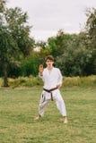 Muchacho confiado del karate en el kimono blanco en un fondo del parque Al aire libre ejercita concepto Copie el espacio Imágenes de archivo libres de regalías