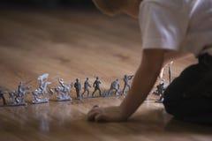 Muchacho cosechado con Toy Soldiers On Floor Foto de archivo libre de regalías