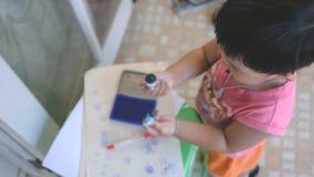 Muchacho creativo que usa la matriz con tinta azul y el sello en el papel como ilustraciones de la opinión de alto ángulo