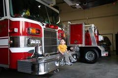 Muchacho curioso que se sienta en un coche de bomberos fotografía de archivo