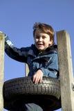 Muchacho cvlimbing una torre del neumático imagenes de archivo
