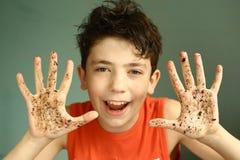 Muchacho dañoso feliz del adolescente con las manos sucias Foto de archivo libre de regalías