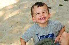 Muchacho de 3 años en la risa de la arena Imagen de archivo libre de regalías