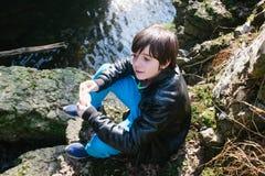 Muchacho de 12 años que come el bocadillo afuera en naturaleza Imágenes de archivo libres de regalías
