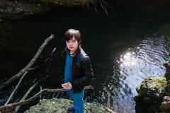 Muchacho de 12 años que come el bocadillo afuera en naturaleza Imagen de archivo