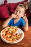 Muchacho de 4 años que come la pizza en un restaurante Foto de archivo libre de regalías