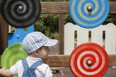 Muchacho de 2 años que juega con el disco espiral de madera en el patio Imagenes de archivo