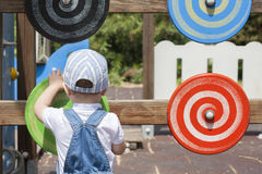 Muchacho de 2 años que juega con el disco espiral de madera en el patio Imágenes de archivo libres de regalías