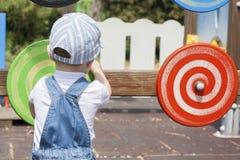 Muchacho de 2 años que juega con el disco espiral de madera en el patio Fotos de archivo