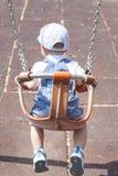 Muchacho de 2 años que juega en el oscilación adaptado Fotos de archivo libres de regalías