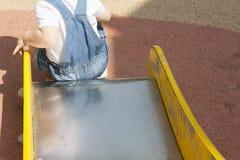 Muchacho de 2 años que juega en el resbalador en el patio Imagen de archivo libre de regalías