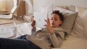 Muchacho de 8 años que miente en una cama y que usa la tableta digital almacen de metraje de vídeo