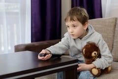 Muchacho de 7 años que se sienta en el sofá y la TV de observación Imagen de archivo libre de regalías