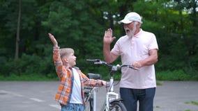 Muchacho de abuelo feliz de la enseñanza cómo montar la bicicleta en el parque del verano familia, generación, seguridad y concep almacen de video