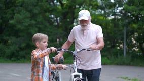 Muchacho de abuelo feliz de la enseñanza cómo montar la bicicleta en el parque del verano familia, generación, seguridad y concep almacen de metraje de vídeo
