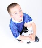 Muchacho de arrodillamiento que sostiene un balón de fútbol Imágenes de archivo libres de regalías