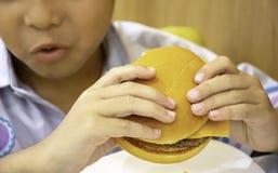 Muchacho de Asia de los pescados y del queso de la hamburguesa a disposición que celebra la consumición imagenes de archivo