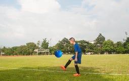 Muchacho de Asia que juega la línea bola b de la hierba del estadio del campo de fútbol del fútbol Imagenes de archivo